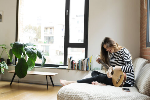 Happy young woman sitting on couch at home playing guitar - VABF02028