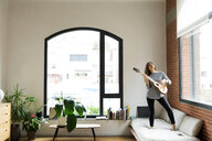 Happy young woman standing on couch at home playing guitar - VABF02031