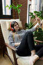 Young woman sitting in armchair at home listening to music with headphones taking a selfie - VABF02037
