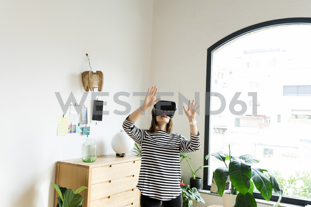 Young woman at home wearing VR glasses - VABF02043