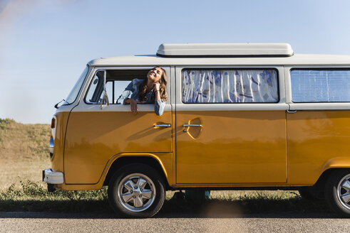 Pretty woman on a road trip with her camper, looking out of car window - UUF16130