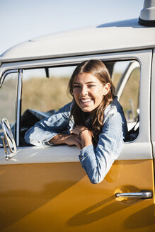 Pretty woman on a road trip with her camper, looking out of car window - UUF16133