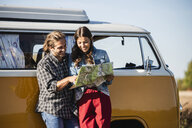 Couple on a road trip in their camper, looking at map - UUF16139