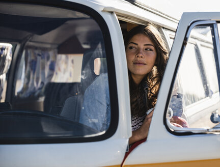 Pretty woman on a road trip with her camper, looking out of car window - UUF16148