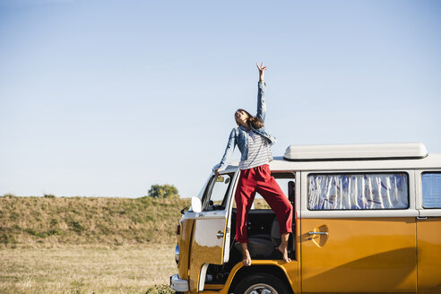 Pretty woman on a road trip with her camper, cheering, enjoying freedom - UUF16151