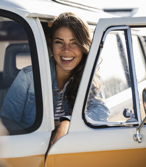 Pretty woman on a road trip with her camper, looking out of car window - UUF16154