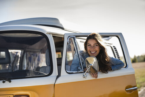 Pretty woman on a road trip with her camper, looking out of car window - UUF16157