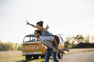Happy couple doing a road trip with a camper, pretending to fly on the road - UUF16205