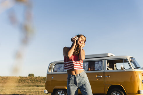 Pretty woman on a road trip with her camper, dancing, listening music - UUF16232