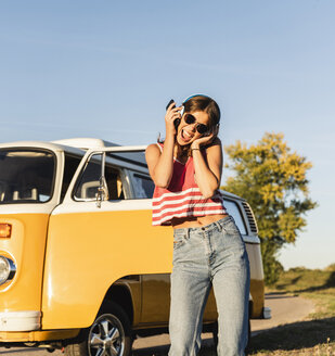 Pretty woman on a road trip with her camper, dancing, listening music - UUF16235