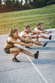Sporty team during workout, standing on one leg, balance training - HMEF00128
