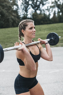 Sportive woman training with barbell, outdoor - HMEF00140