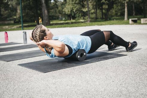 Sportive woman training with fascia roll - HMEF00149