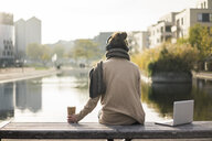Back view of woman sitting on bench  with laptop and coffee to go listening music with headphones - MOEF01829