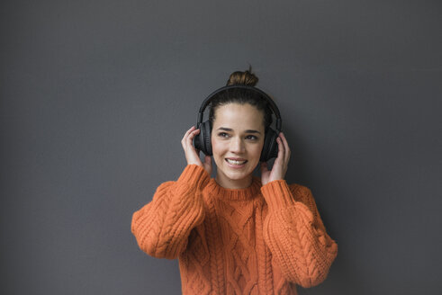 Portrait of smiling woman with headphones wearing orange knit pullover against grey background - MOEF01844