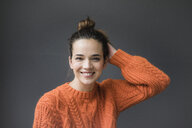 Portrait of happy woman wearing orange knit pullover against grey background - MOEF01850