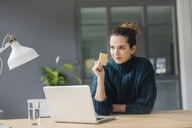 Portrait of confident woman with laptop and credit card sitting at desk at home looking at distance - MOEF01853