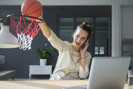 Portrait of freelancer on the phone throwing basketball into hoop at workspace - MOEF01856