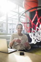 Portrait of smiling freelancer sitting at desk in a loft throwing basketball into hoop - MOEF01859