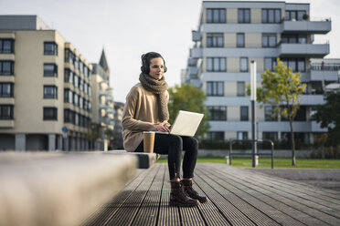 Woman sitting on bench with laptop and coffee to go listening music with cordless headphones - MOEF01865