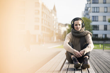 Portrait of woman sitting on bench in autumn listening music with cordless headphones - MOEF01868