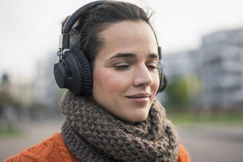 Portrait of smiling woman wearing scarf listening music with cordless headphones - MOEF01883