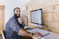 Portrait of happy young architect working at home with blueprints and computer - JRFF02168