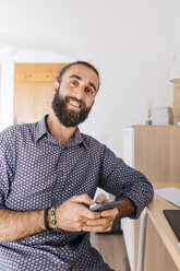 Portrait of smiling young man using cell phone at home - JRFF02177