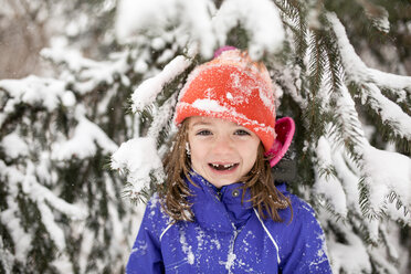 Portrait of cheerful girl wearing warm clothing while standing against snow covered tree - CAVF57969