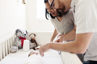 Happy parents looking at newborn daughter lying in crib at home - CAVF58047