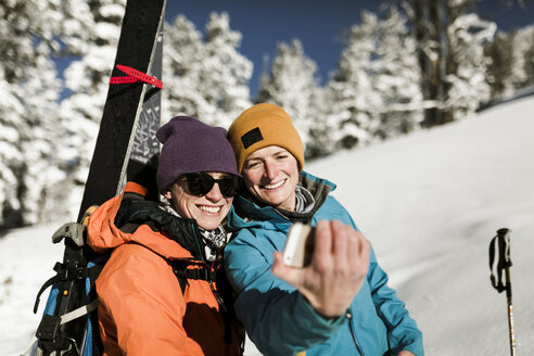 Happy friends talking selfie while standing on snow covered hill - CAVF58080
