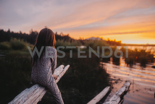 Playful girl looking at view while sitting on driftwood during sunset - CAVF58176