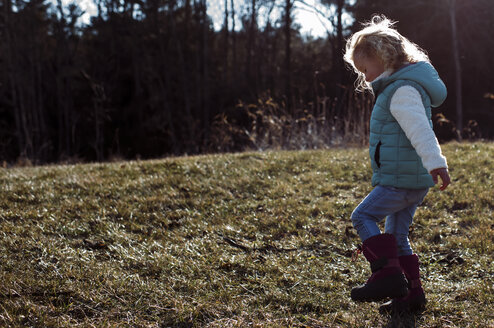 Side view of girl walking on grassy field at park - CAVF58242