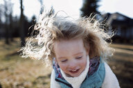 Girl smiling while standing at park - CAVF58245