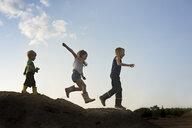 Low angle view of playful siblings walking on rock against sky - CAVF58260