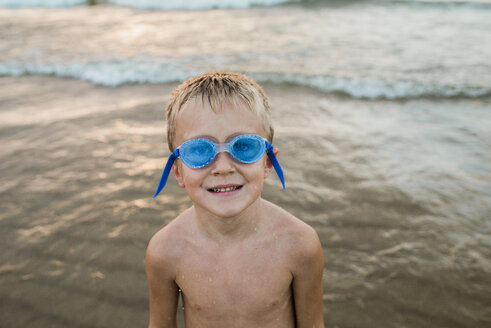 Portrait of shirtless boy wearing swimming goggles while standing on shore at beach - CAVF58266