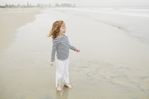 Cheerful girl looking away while standing on shore at beach - CAVF58281