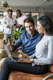 Smiling businessman and businesswoman using laptop on sofa in loft office - GIOF04967