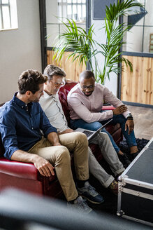 Three businessmen using laptop sitting on sofa in loft office - GIOF04970