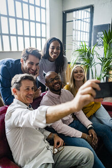 Happy business team taking a selfie in loft office - GIOF05012