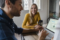Businesswoman smiling at businessman during a meeting in office - GIOF05015