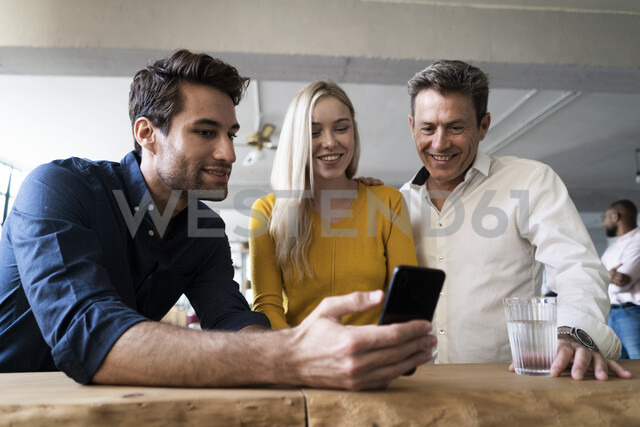Smiling business team looking at cell phone together in loft office - GIOF05033 - Giorgio Fochesato/Westend61