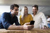 Smiling business team looking at cell phone together in loft office - GIOF05033