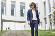 Portrait of young fashionable businessman with curly hair wearing blue suit and sunglasses - JSMF00643