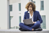 Portrait of young businessman with curly hair wearing blue suit sitting on bench using laptop outdoors - JSMF00652