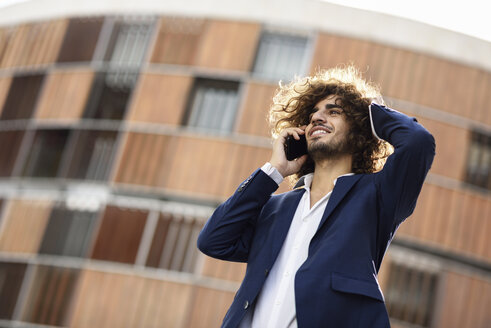 Portrait of young smiling fashionable businessman with curly hair on the phone - JSMF00670