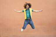 Portrait of smiling young man with curly hair wearing yellow waistcoat jumping in the air - JSMF00676