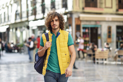 Spain, Granada, portrait of young tourist with backpack discovering the city - JSMF00679