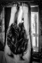 Surreal rear view of a woman with her hair overflowing her body indoors - INGF08752