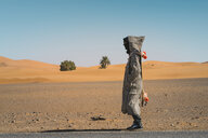 Side view of man with skateboard standing on road in desert against sky during sunny day - CAVF58295